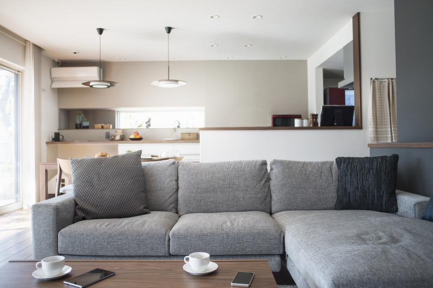 Couch in living room Tan & grey painted accent walls in an interior residential living room & kitchen.