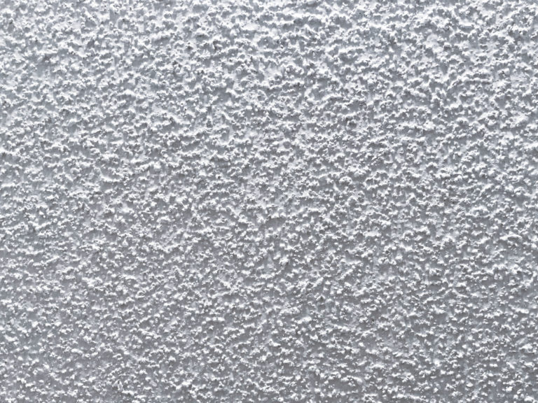 Close-up image of popcorn or textured ceiling.