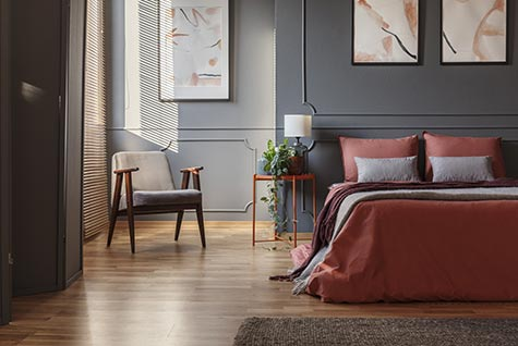 Grey painted interior residential bedroom with double bed.